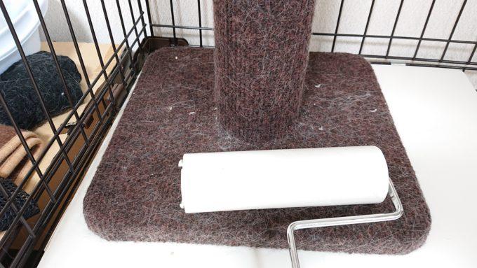 ケージの中に入れた爪みがきポール(コロコロをかけている所)猫の毛を取っている。